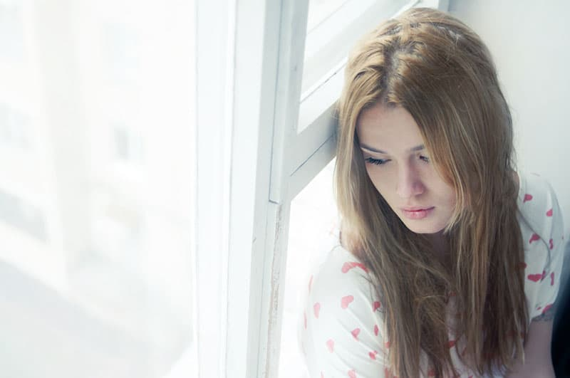 sad young woman sitting by the window
