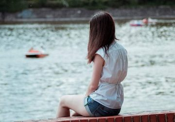woman sitting alone in front of water