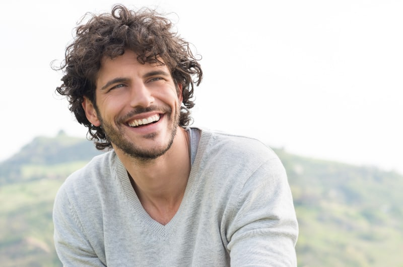 smiling curly haired man wearing shirt outside