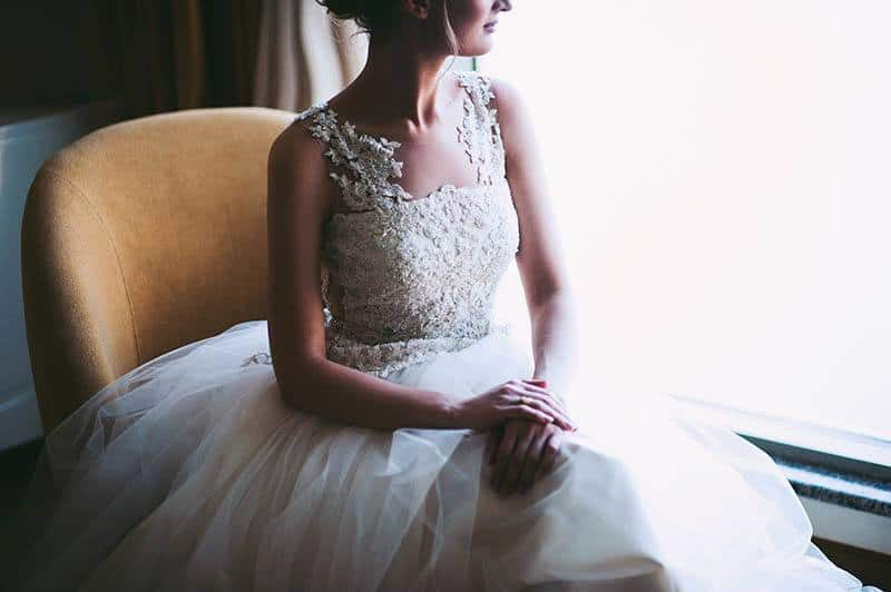 the woman in the wedding dress sitting beside window and looking out