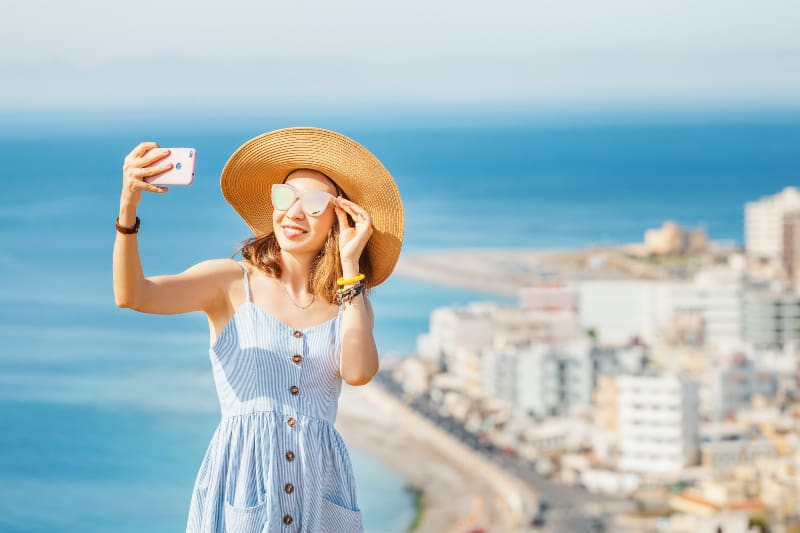 A young stylish girl in a big hat taking selfie