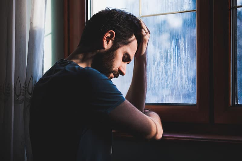depressed man leaning hand on window at home