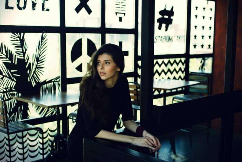 Woman in black quarter sleeve top leaning on black desk