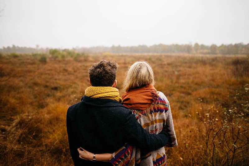 a man and a woman embracing in a field