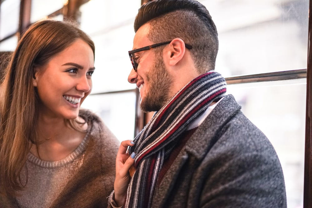 a man and a woman look at each other and laugh