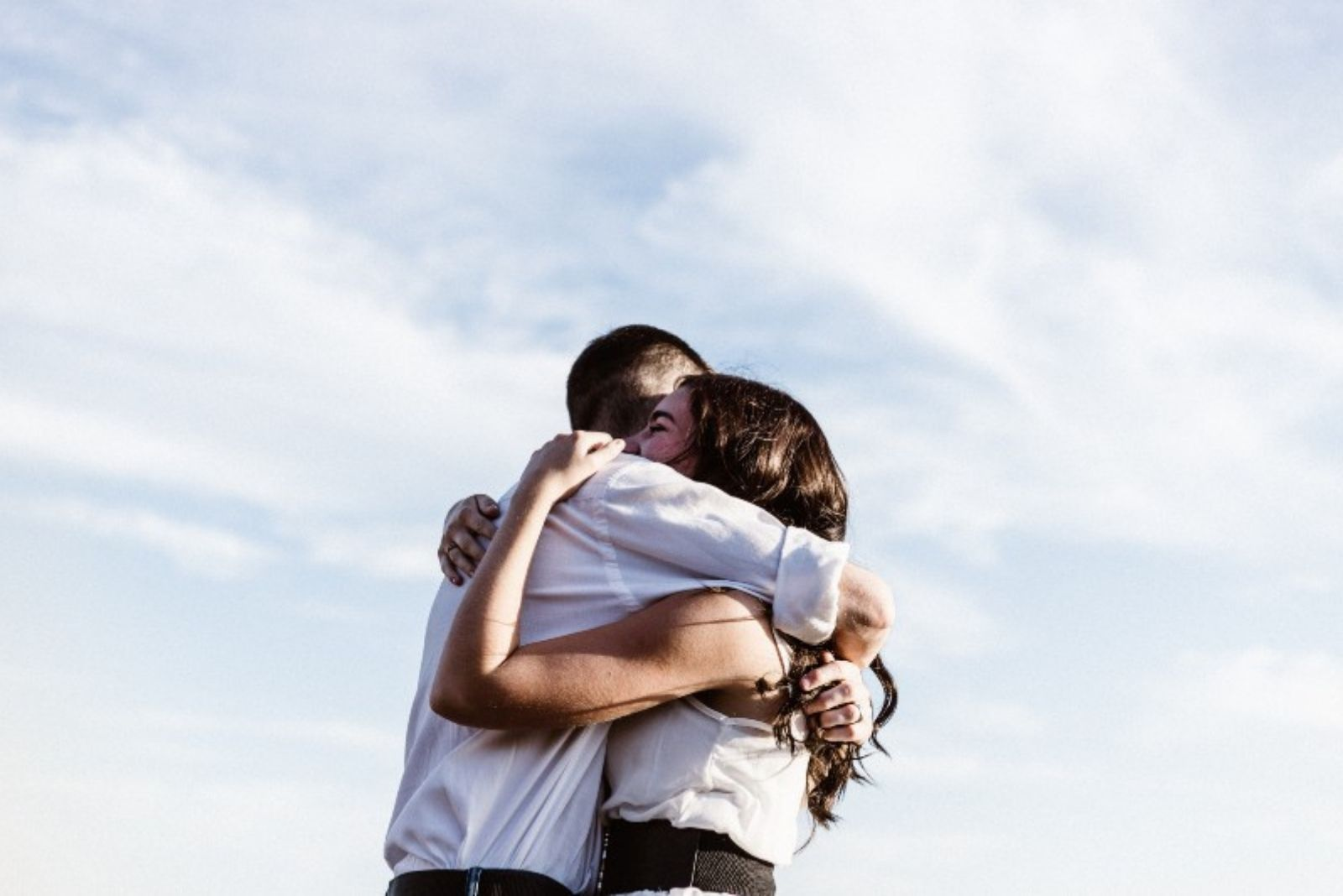 a man and a woman stand embracing
