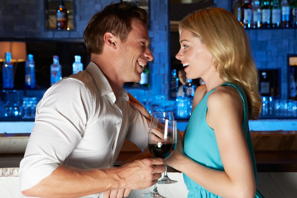a man and a woman standing in a club laughing