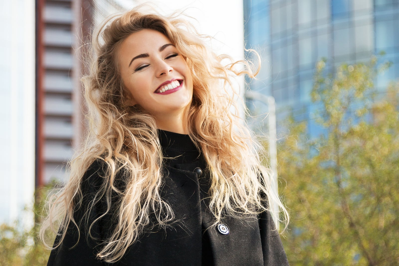 a portrait of a smiling blonde in a black coat