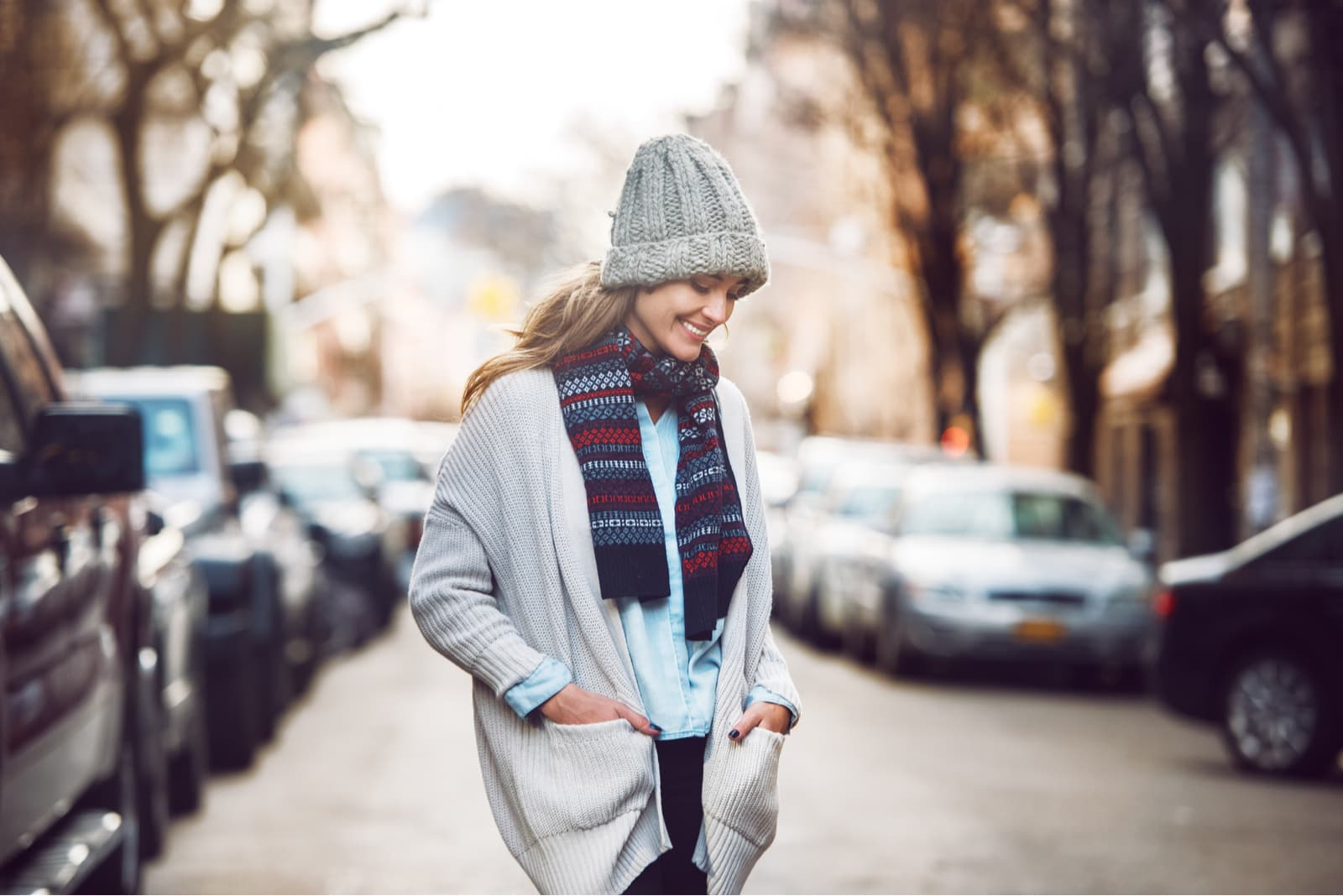 a smiling woman in a sweater with a hat and scarf walks down the street