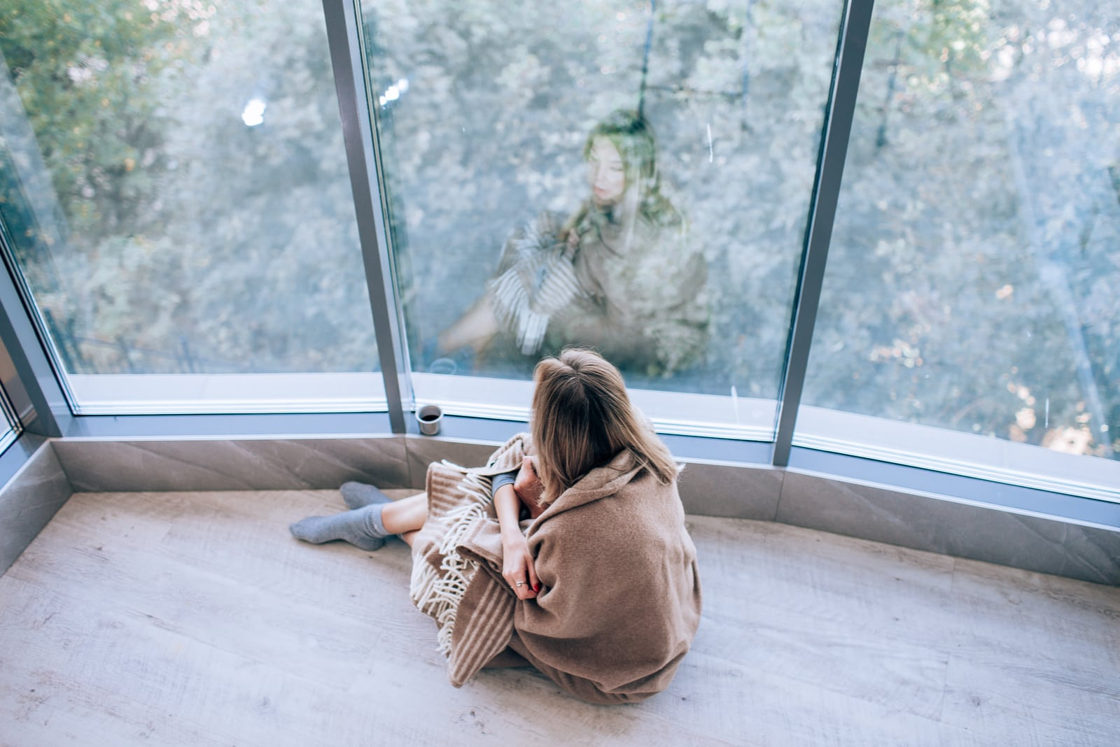 a woman sits on the floor by the window and drinks coffee
