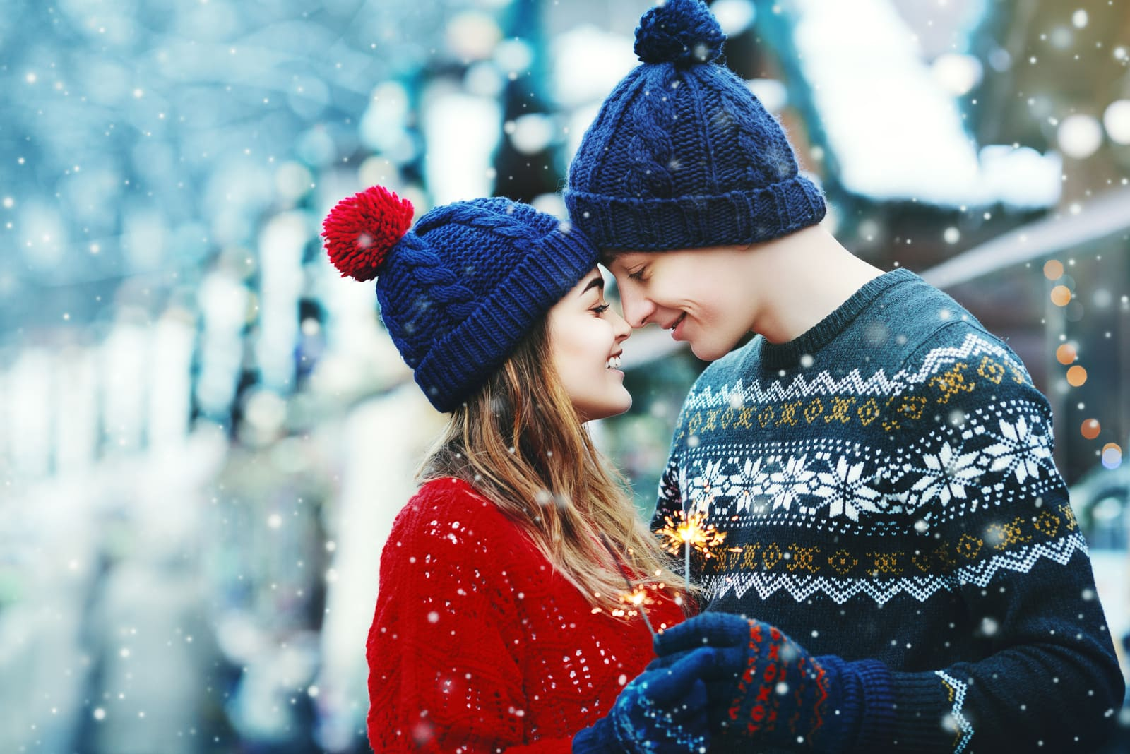 a young loving couple hugging and kissing outside in the snow