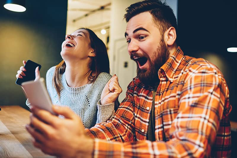 Excited male and female hipsters rejoice in winning an internet lottery