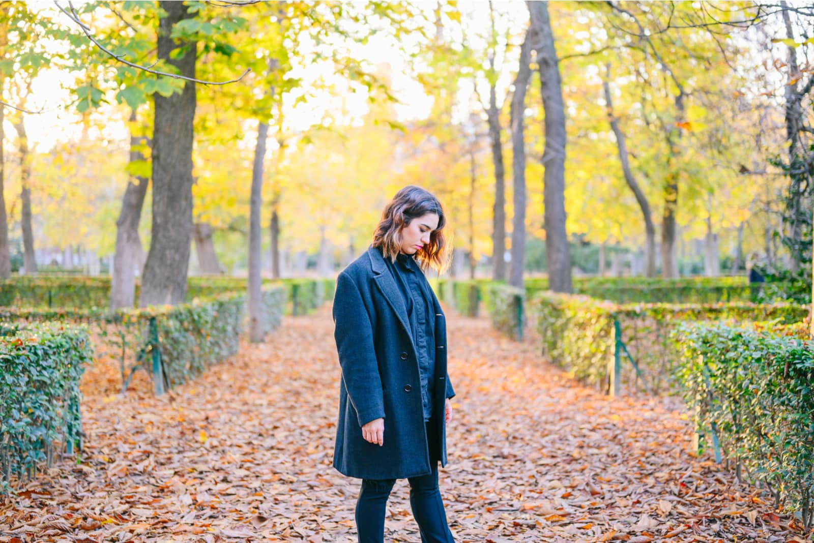 autumn in the park stands a sad woman