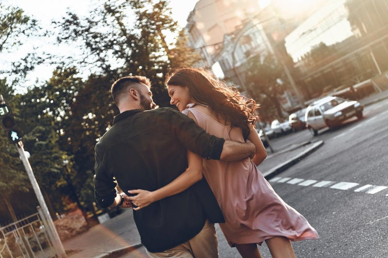 back view of couple smiling and looking each other while crossing street