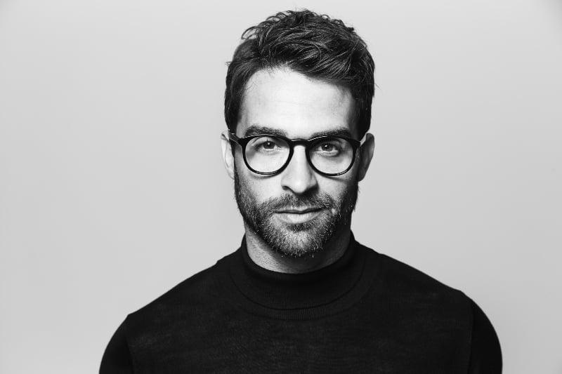 black and white photo of bearded man wearing eyeglasses