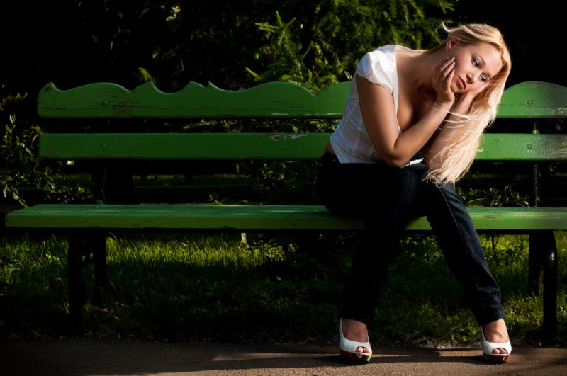 blond woman wearing white shirt sitting on the bench