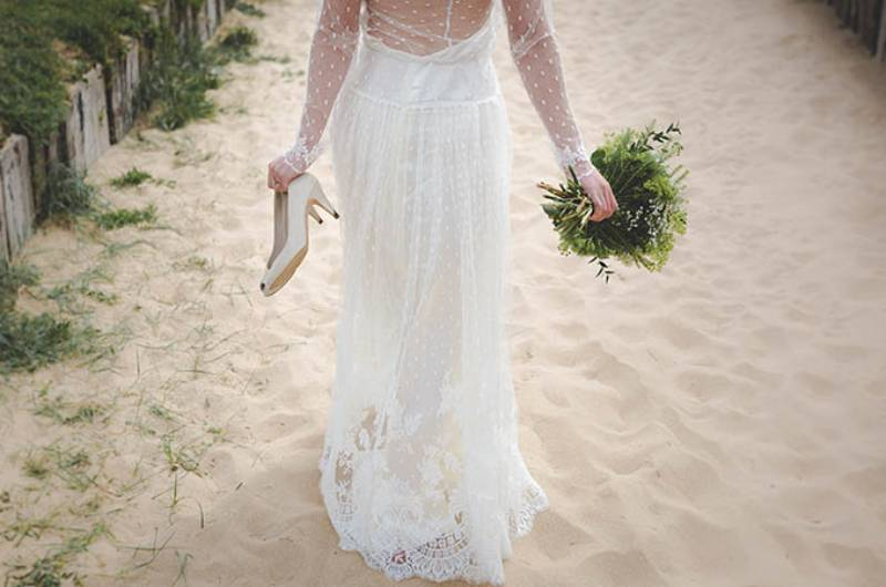 bride woman walking on sand with flowers and heels in hands