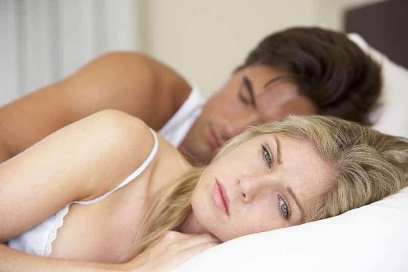 concerned blonde woman lying in bed next to her boyfriend