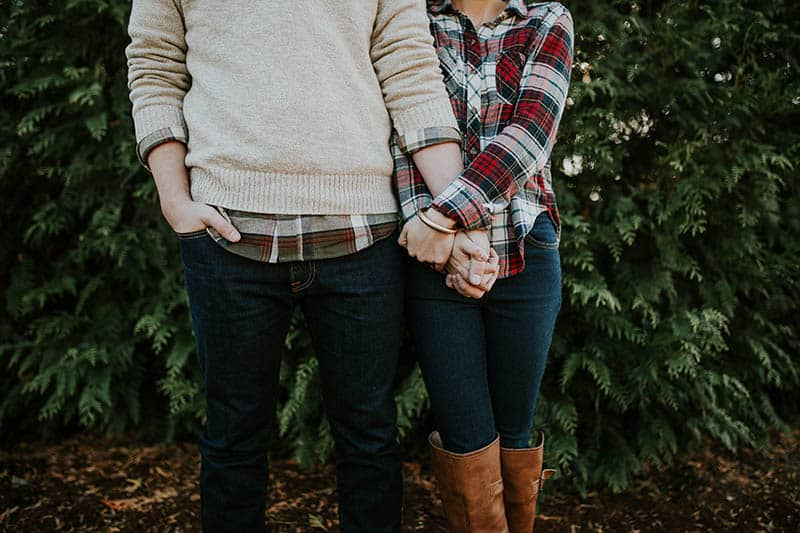 couple holds their hands outside