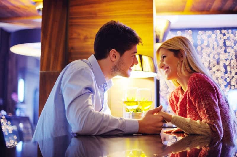 couple looking each other while holding hands in cafe