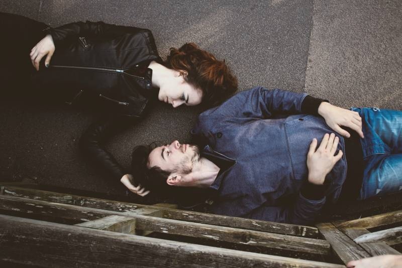 couple lying on street and looking at each other