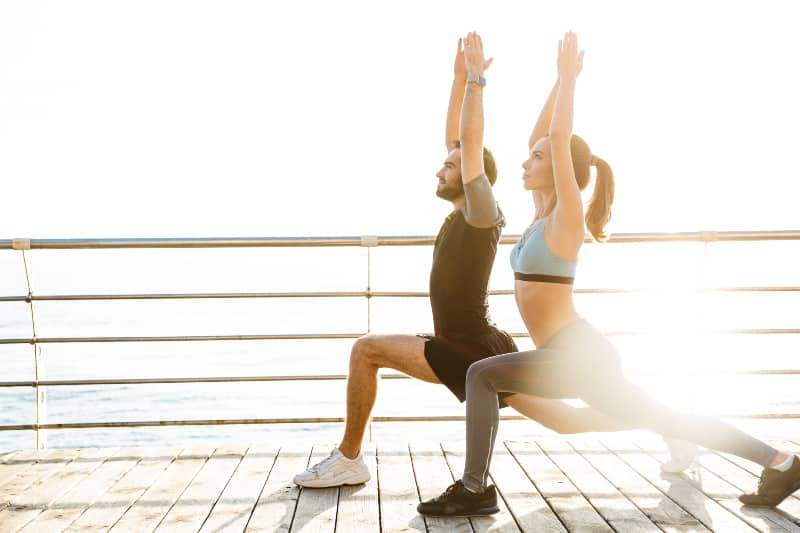 couple stretching beside water during daytime