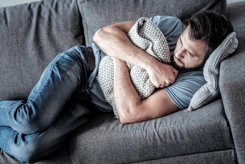 depressed man hugging pillow while lying on couch at home