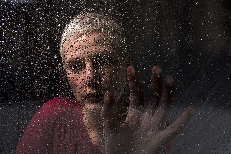 depressed woman sitting by the rainy glass