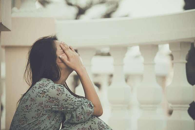 depressed woman sitting on the balcony floor