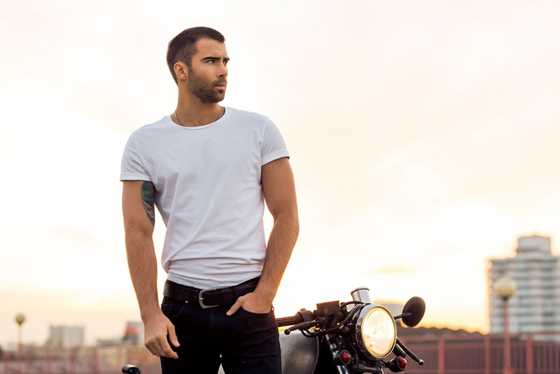 handsome man standing with motorbike