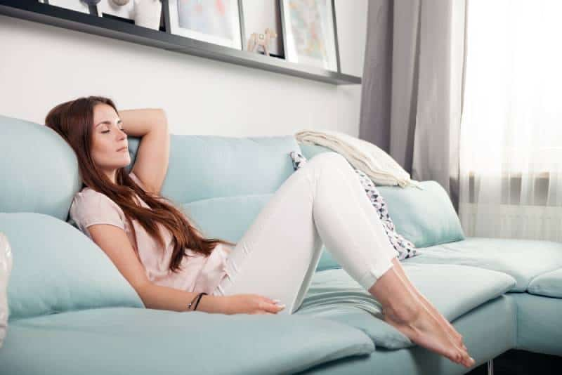 happy young woman lying in living room and relaxing