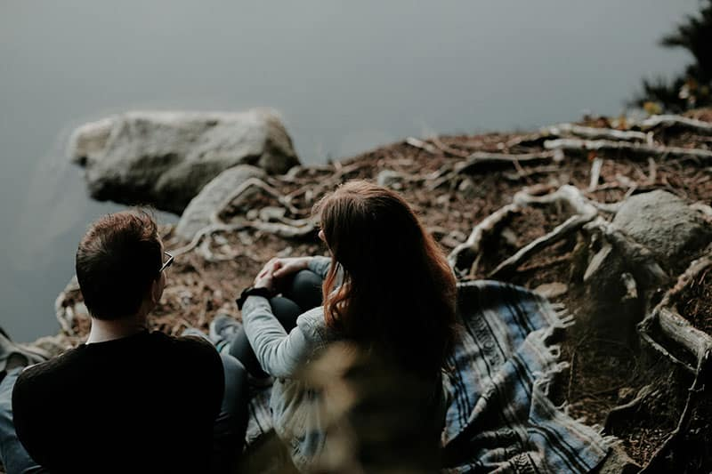 high angle of man and woman talking in front of lake