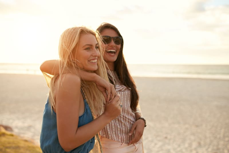 laughing female friends standing beside sea