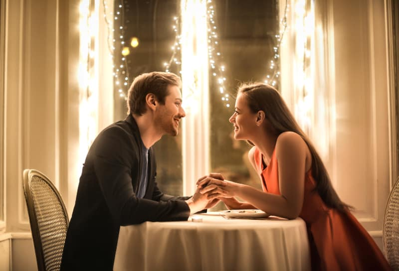 lovely couple looking each other and holding hands in restaurant