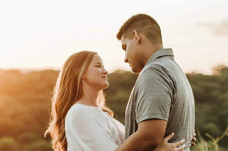 lovely couple looking each other during golden hour outside