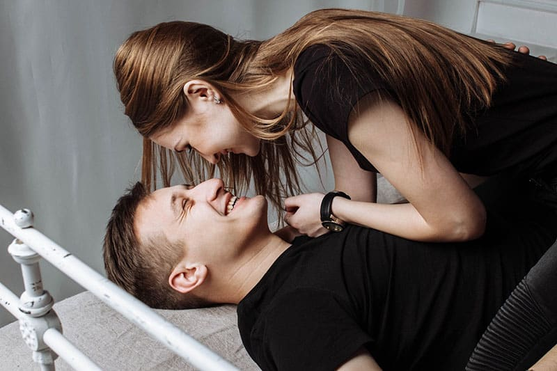 lovely couple smiling in bedroom