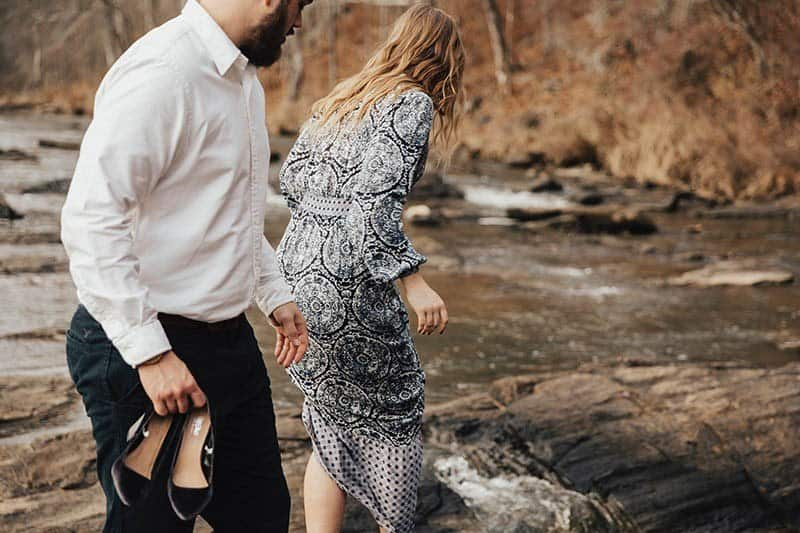 man holds woman heels while she walking on wet rocks