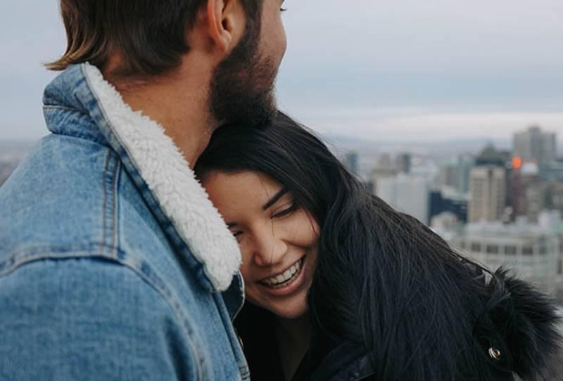 man hugging smiling woman