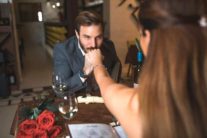 man kissing woman's hand at date