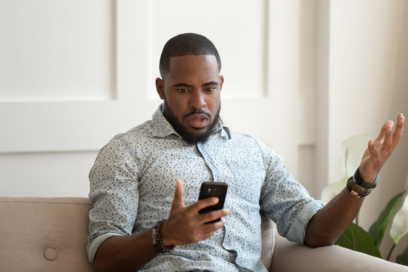man looking at phone looks confused