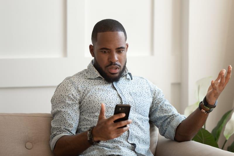 man looking at phone looks confused