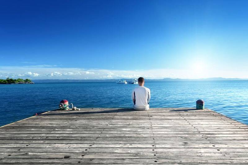 man sitting alone on boat dock in front of sea