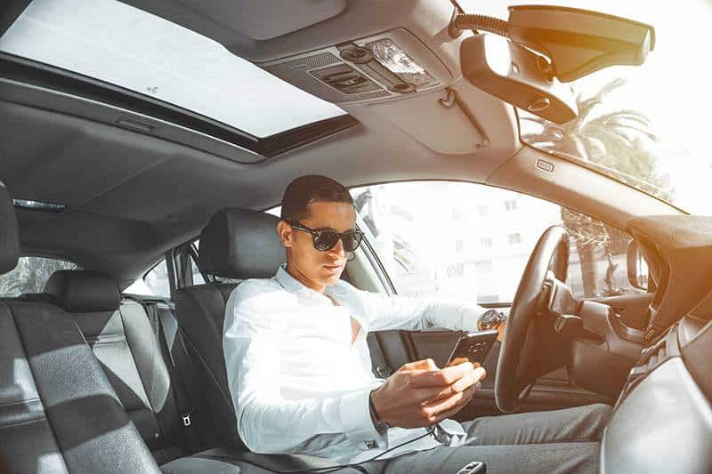 man typing on his phone while driving car