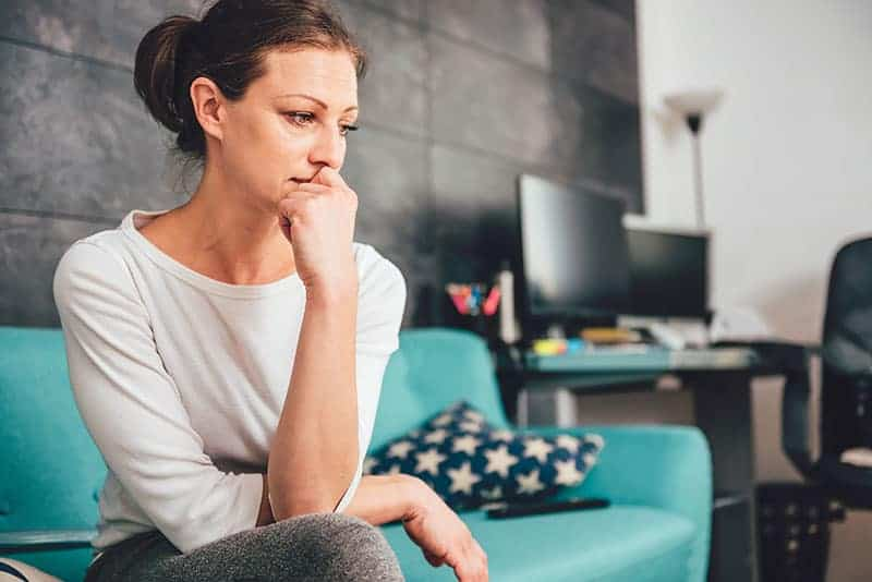 mindful worried woman sitting on the couch