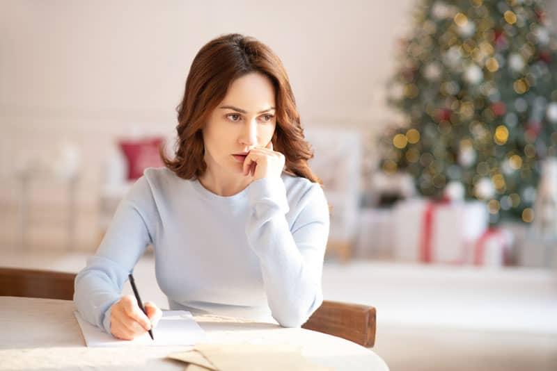 sad mindful woman writing a letter