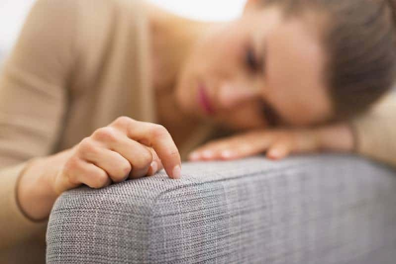 sad woman lying in living room and thinking