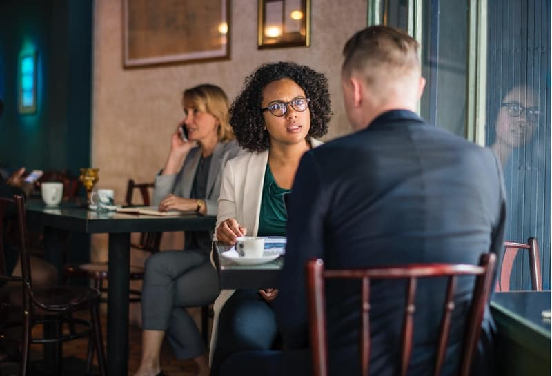 serious woman talking to a man in cafe