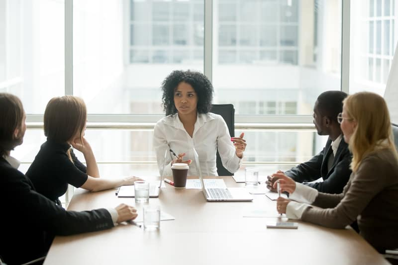 female boss leading corporate multiracial team