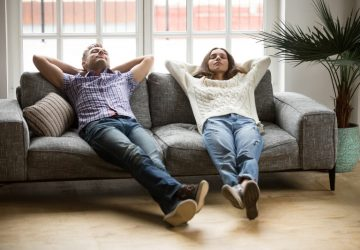 man and woman relaxing at home on sofa