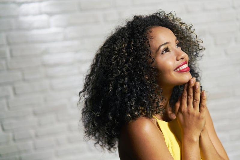 woman smiling and saying prayer